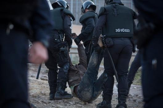 Un des migrants est arrêté par la police.